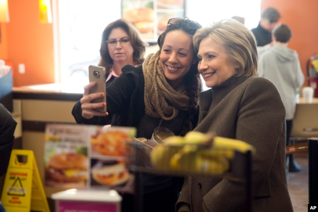 Democratic presidential candidate Hillary Clinton makes a selfie with a customer Sunday, Feb. 7, 2016, at a Dunkin' Donuts in Manchester, N.H.