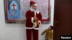 2018年12月22日,中国云南省鹿泉彝族苗族自治县的基督教堂,一个男孩看着圣诞老人像。