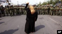一名維吾爾族婦女在中國警察面前抗議(資料圖片)