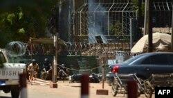 Des militaires se protègent alors que de la fumée s'échappe de l'Institut français de Ouagadougou, Burkina Faso, le 2 mars 2018