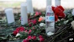 Una botella de agua, flores, velas y peluches fueron depositados en el lugar donde las autoridades descubrieron el sábado un tráiler lleno de inmigrantes en San Antonio, Texas, el lunes, 24 de julio de 2017. (AP Foto / Eric Gay)