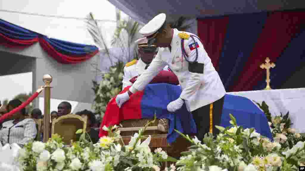 Un policier ajuste le drapeau sur le cercueil contenant les l'ancien président René Préval lors du service à Port-au-Prince, Haïti, le samedi 11 mars 2017.