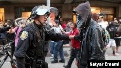 Un oficial de policía detiene a uno de los manifestantes.