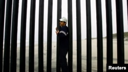 Jorge Alverez of Mexico crosses the wall border between Mexico and the United States at the beach of Tijuana, Mexico May 6, 2006. REUTERS/Carlos Barria