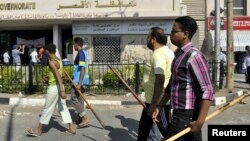 Protesters, armed with sticks, gather in front of the Luxor governorate building to protest the appointment of Adel Mohamed al-Khayat as governor, Luxor, June 19, 2013.