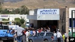 Quelques personnes se tiennent devant le service des urgences de l'hôpital de Kasserine, Tunisie, 17 juillet 2014.