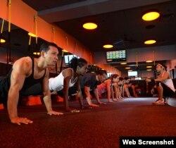심박자 맞춤 운동을 제공하는 오렌지띠어리(Orange Theory) 체육관에서 회원들이 강사의 지도를 받으며 움직이고 있다. 심장박동을 측정하는 디지털 화면이 걸려있다.