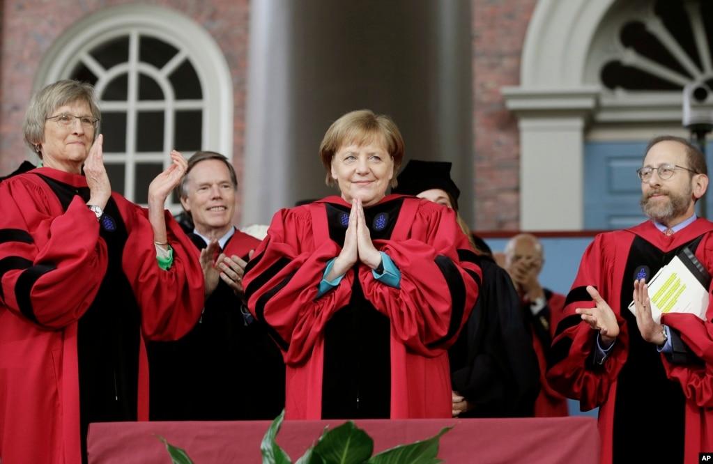 Канцлер Германии Ангела Меркель, центр, признает аплодисменты, когда она получает почетную степень доктора юридических наук, в то время как бывший президент Гарварда Дрю Фауст, левый и Гарвардский проректор Алан Гарбер, справа, смотрят во время учений Гарвардского университета в Кембридже, штат Массачусетс.