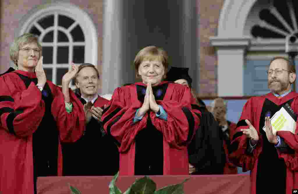 German Chancellor Angela Merkel, center, acknowledges the applause as she receives an honorary Doctor of Laws degree, while former Harvard President Drew Faust, left, and Harvard Provost Alan Garber, right, look on during Harvard University Commencement Exercises in Cambridge, Massachusetts.