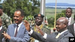 Ugandan President Yoweri Museveni (R) and Eritrean President Isaias Afewerki wave as Afewerki arrived in Uganda for a three-day visit, August 16, 2011