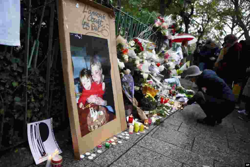 Seorang perempuan menyalakan lilin-lilin untuk menghormati para korban serangan maut di Paris tahun lalu, di depan gedung konser Bataclan (13/11). (AP/Francois Mori)