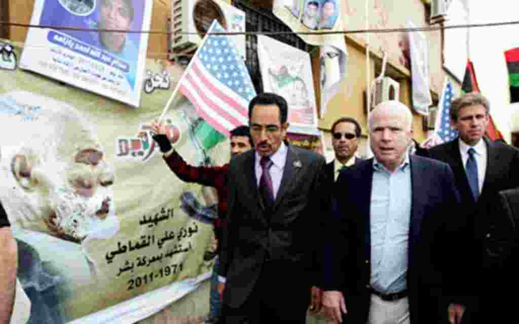 US Rebuplican senator John McCain (R) walks with Abdul Hafiz Ghoqa, spokesman of the Libyan National Transitional Council (NTC), during his tour to the rebel headquarters in their eastern stronghold city of Benghazi , April 22, 2011