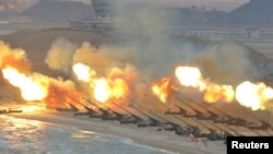FILE - Artillery pieces are seen being fired during a military drill at an unknown location, in this undated photo released by North Korea's Korean Central News Agency (KCNA) on March 25, 2016.