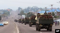 FILE - Congo military trucks carrying Congolese troops drive in a main street after violence erupted due to the delay of the presidential elections in Kinshasa, Democratic Republic of Congo, Tuesday, Sept. 20, 2016.