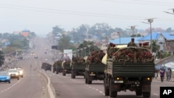 FILE - Congo military trucks carrying Congolese troops drive in a main street after violence erupted due to the delay of the presidential elections in Kinshasa, Democratic Republic of Congo, Sept. 20, 2016.