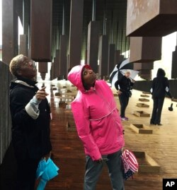 Kim McRae of Laurel, Md., left, and Melodi McNeil of Silver Spring, Md., look at commemorative markers listing lynching victims at the National Memorial for Peace and Justice in Montgomery, Ala., April 26, 2018.