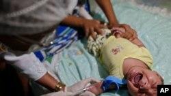 Un trabajador de salud extrae una muestra de sangre a un niño nacido con microcefalia en Joao Pessoa, estado de Paraíba, uno de los estados más pobres de Brasil y epicentro de un brote de Zika y de microcefalia.