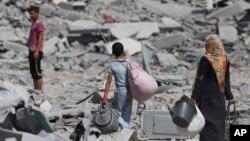 Người dân Palestine đem theo đồ đạc còn sót lại sau khi nhà của họ ở thị trấn Beit Hanoun, dải Gaza, gần biên giới với Israel, bị những trận bom tàn phá nặng nề.