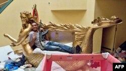 Libijski pobunjenik u jednoj od raskošnih soba u ogromnom kompleksu Moamera Gadafija, u Tripoliju