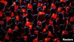 Performers hold flags of the Communist Party of China during an event to celebrate the 90th anniversary of the founding of the party, at the Mercedes-Benz Arena in Shanghai, on June 30, 2011. (Reuters/Carlos Barria)