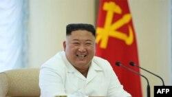 Kantor berita Korea Utara KNCA merilis foto pemimpin Korea Utara Kim Jong Un yang sedang tersenyum saat menghadiri pertemuan Biro Politik ke-13, 7 Juni 2020. (Foto: AFP)
