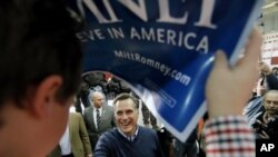 Republican presidential candidate and former Massachusetts Governor Mitt Romney is framed by a campaign sign held by a supporter as he greets the crowd after a campaign rally at Pinkerton Academy in Derry, New Hampshire, January 7, 2012.