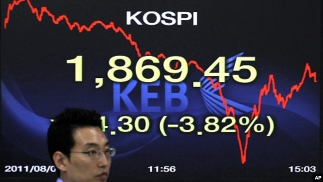 A foreign currency dealer of the Korea Exchange Bank walks past a screen displaying the Korea Composite Stock Price Index (KOSPI) at the bank's dealing room in Seoul August 8, 2011.