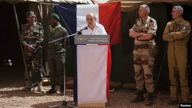 French Defense Minister Jean-Yves Le Drian addressing troops at a military encampment at a Malian air base, Gao, March 7, 2013.