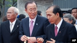 U.N. Secretary-General Ban Ki-moon (center) is escorted around the former security prison known as S-21 with a guide (right). The commandant of S-21, Comrade Duch, was convicted by the war crimes tribunal in Phnom Penh earlier this year.