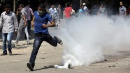 An Egyptian protester runs away from a tear gas canister fired by riot police, near street leading to US embassy during clashes in Cairo, Egypt, Sept 14, 2012.