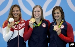 United States' gold medal winner Lilly King is flanked by Russia's silver medal winner Yulia Efimova, left, and United States' bronze medal winner Katie Meili during the ceremony for the women's 100-meter breaststroke final during the swimming competitions at the 2016 Summer Olympics, Tuesday, Aug. 9, 2016.