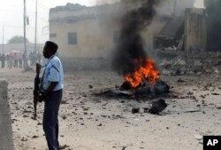 Policier somalien debout près d'une voiture détruite dans une explosion à Mogadiscio, le 6 décembre 2011