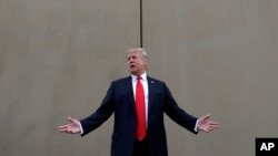 FILE - President Donald Trump speaks during a tour as he reviews border wall prototypes in San Diego, California, March 13, 2018.