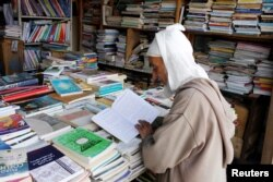 An elderly man reads a book in a bookshop in Bab Doukkala in the city of Marrakech, Morocco, May 13, 2017.