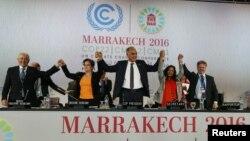Le responsable du climat à l'ONU, Patricia Espinosa, deuxième à gauche, la ministre des Affaires étrangères du Maroc, Salaheddine Mezouar, au centre et l'ambassadeur de bonne volonté du Conseil de l'Europe, Bianca Jagger, deuxième à droite, célèbrent après la proclamation de Marrakech, lors de la cérémonie de clôture de la Conférence mondiale sur le climat de l'ONU, à Marrakech, Maroc, 17 novembre 2016.