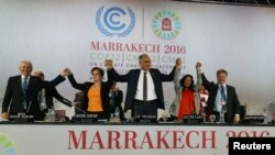 U.N. climate chief Patricia Espinosa, second left, Morocco's Foreign Minister Salaheddine Mezouar, center, and Council of Europe Goodwill Ambassador Bianca Jagger, second right, celebrate after the proclamation of Marrakech, at the U.N. World Climate Chan