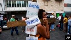 Una manifestante antigubernamental lleva una cruz con sus reclamos al gobierno, durante el viacrucis del venezolano, celebrado ayer en Caracas.
