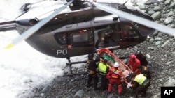 In this photo provided by the government news agency Andina, rescue workers surround an injured man on a stretcher who was lifted up from the site of a bus crash at the bottom of a cliff, after the bus was hit by a tractor-trailer rig in Pasamayo, Peru, J