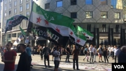 Syrians gather in a Vienna square to inform the public about the gruesome war in Syria, July 3, 2016. Refugees say many people don't realize they had no choice but to flee. (H. Murdock/VOA)