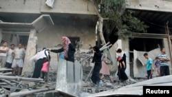 Warga Palestina memeriksa rumahnya yang terkena serangan udara Israel di kota Gaza (10/7).
