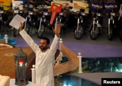 "FILE - Aamir Liaquat Hussain, host of the Geo TV channel program ""Amaan Ramazan,"" gestures while asking participants questions during a live show in Karachi, July 26, 2013."