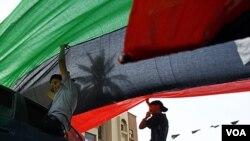 Jamal Goubtan, quien es residente en Libia, ayuda a desplegar una gigantesca bandera en Trípoli.