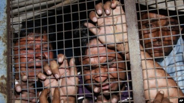 People charged in connection of setting a building on fire weep inside a police vehicle as they are taken to a prison after their hearing in a court at Mehsana, about 60 km (37 miles) north from the western Indian city of Ahmedabad. (File Photo - November