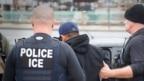 Nhân viên Cơ quan Di trú và Hải quan Hoa Kỳ (ICE) áp giải một nghi phạm gốc Á.