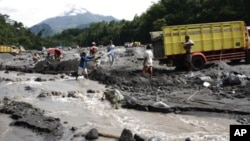 Sand miners collecting sand flowed from the eruption of Mount Merapi, as seen in the background.