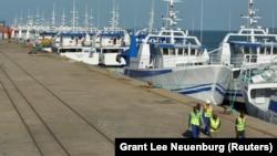 Patrulha de segurança passa por barcos da EMATUM na doca de Maputo.
