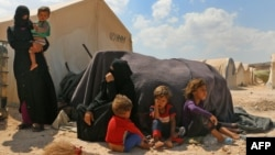FILE - Displaced Syrians are seen at a camp near the border crossing with Turkey in the northern part of Syria's rebel-held Idlib province, Sept. 6, 2018.
