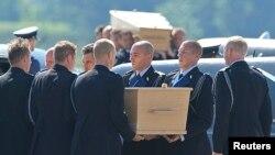 馬航MH17班機部份遇難者的遺體靈柩7月23日抵達荷蘭埃因霍恩機場。機場上舉行了接機儀式。遇難者的靈柩正在被從抬下飛機,安放在靈柩車裡。