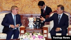 문재인 한국 대통령(오른쪽)이 지난 7월 청와대에서 토마스 바흐 국제올림픽위원회(IOC) 위원장을 만나 대화하고 있다.