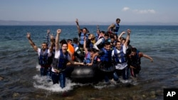 Un bateau pneumatique plein des réfugiés et migrants accostent sur la rive à l'ïle de Lesbos, en Grèce, 11 septembre 2015.